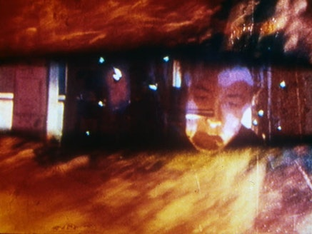 Barbara Hammer, 16 mm film frame from <i>Endangered</i> (1988). Shows the artist working on an optical printer with abstract images.