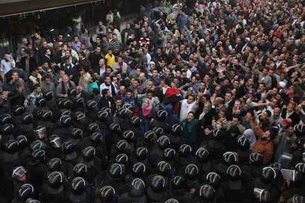 Egyptian protesters face anti-riot policemen in Cairo on Friday, Jan. 28, 2011. The riots escalated throughout the day. Victoria Hazou / AP.