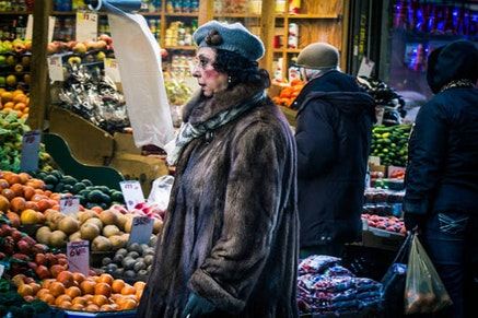 Smoking a cigarette and observing the fruit stands, she seemed like a film noir character.