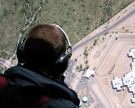 "Christoph Gielen – Dispatch | ""Supermax Prisons: Views from Above"" – USA. (c) Nina Gielen, ""Christoph Gielen surveys Arizona's Florence State Prison from a helicopter,"" 2010."