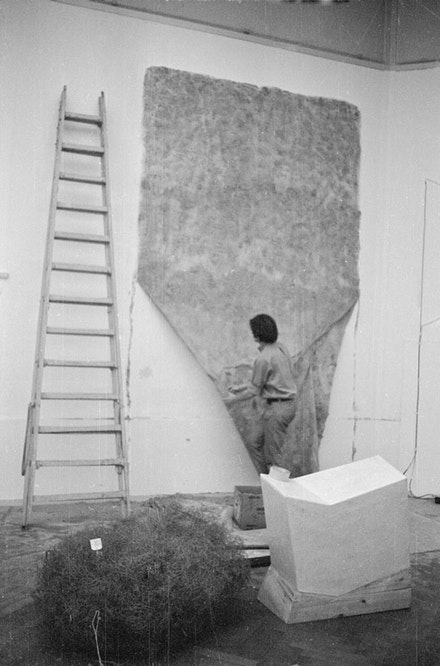 "Installation view of <i>When Attitudes Become Form</i>. Keith Sonnier installing ""Flocked Wall,"" 1969. From left to right, works by Alan Sarret and Gary B. Kuehn. Kunsthalle Bern, Switzerland, 1969. Courtesy the Getty Research Institute, Los Angeles. Photo: Balthasar Burkhard. © J. Paul Getty Trust"