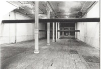 """Jene Highstein, """"Two Horizontals,"""" 1974, seamless steel pipe. 112 Greene Street, New York. Two 16-inch diameter seamless steel pipes suspended from the walls and spanning the room at different heights, the lowest 6'4"""" high and the highest 8' 8"""" high, each 36' long. Panza di Biumo Collection. Photo (c) Gianfranco Gorgoni."""