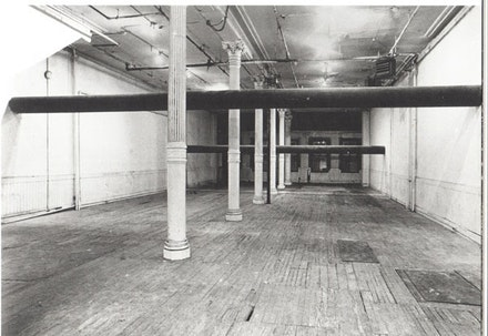 "Jene Highstein, ""Two Horizontals,"" 1974, seamless steel pipe. 112 Greene Street, New York. Two 16-inch diameter seamless steel pipes suspended from the walls and spanning the room at different heights, the lowest 6'4"" high and the highest 8' 8"" high, each 36' long. Panza di Biumo Collection. Photo (c) Gianfranco Gorgoni."