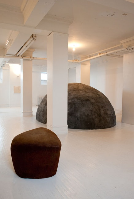 "Jene Highstein, ""Mound for Suzi,"" 1976 (recreated 2013). Concrete, chicken wire, black pigment, and wood. 12 x 18 x 6.5'. © 2013 Selina Highstein."