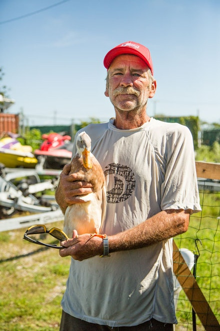 Parkway Marina mechanic Harry holds Daffy, a duck, one of several semi-aquatic animals he cares for year round.