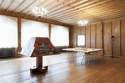 """Jill Magid, """"Der Trog"""" 2013. Facistol (Pine lectern inspired by Luis Barragán, mounted reproductions from Luis Barragán's personal archive) and architectural model, variable dimensions, 200 x 200 x 15 cm (78.74 x 78.74 x 5.91 in) model in two parts. Exhibition view Art Basel 2013."""