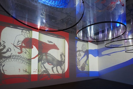 """Detail view of Nalini Malani's installation """"In Search of Vanished Blood"""" 2012, six-channel video/shadow play with five rotating reverse painted Mylar cylinders, sound, 11 minutes, total dimensions variable, edition of 3; at Lelong, © Nalini Malani, Courtesy of Galerie Lelong, New York."""