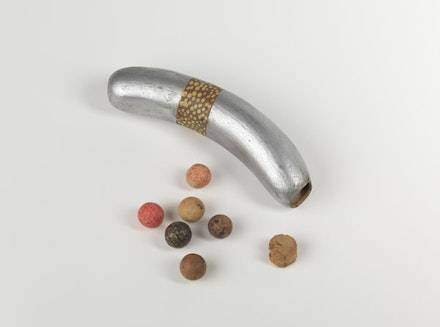 "Robert Watts, ""Flux Rattle from the Yam Festival Delivery Event,"" 1962–3. Plastic hotdog, cork, clay balls, and paint, 14 x 3.2 x 3.8 cm. Courtesy and © Robert Watts Estate, New York. Photo Bruce M. White."