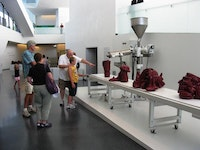"Roxy Paine, Visitors viewing ""Scumak No. 2"" at The Nelson-Atkins Museum of Art, Kansas City, Missouri, 2011. Aluminum, computer, conveyor, electronics, extruder, stainless steel, polyethylene, Teflon, 90 × 276 × 73 ̋. Photography by Adrianne Russell."