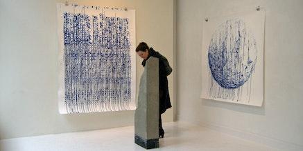 The Danish art critic Lisbeth Bonde studying a concrete sculpture by the young Danish artist Søren Pihlmann at Martin Asbaek's Gallery.
