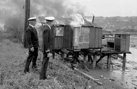 Naval Officers oversee a burning shack in Seattle's Hooverville. Source: University of Washington Libraries, Seattle Post-Intelligencer Collection. In the Museum of History and Industry, Seattle repository.