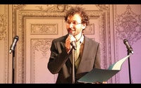 Adam Horowitz as Norman Beckett, USDAC Deputy Secretary, hosting the People's State of the Union at the Bowery Poetry Club.