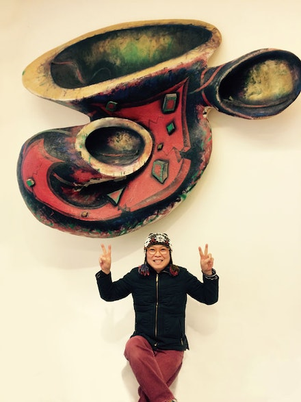 "Phong Bui in front of Elizabeth Murray, ""Stay Awake"" (1989). Oil on canvas laid on wood construction, 70 × 89 × 23 ̋. Courtesy Murray-Holman Family Trust. As exhibited on the Elizabeth Murray Art Wall in its home at Howl! Happening, a new gallery/performance space at 6 East 1st St, just across the street from the Bowery Poetry Club which Elizabeth helped found and which was the site of the original EMAW."