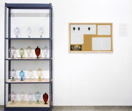 "Josiah McElheny, <em>The Controversy Surrounding the ""Veronese"" Vase (From the Office of Luigi Zecchin)</em>, 1996. Blown glass, metal shelving, bulletin board, drawings and text, 84 x 35 1/2 x 12 inches (shelving), 37 1/2 x 25 1/4 inches (bulletin board). Courtesy Andrea Rosen Gallery, New York."