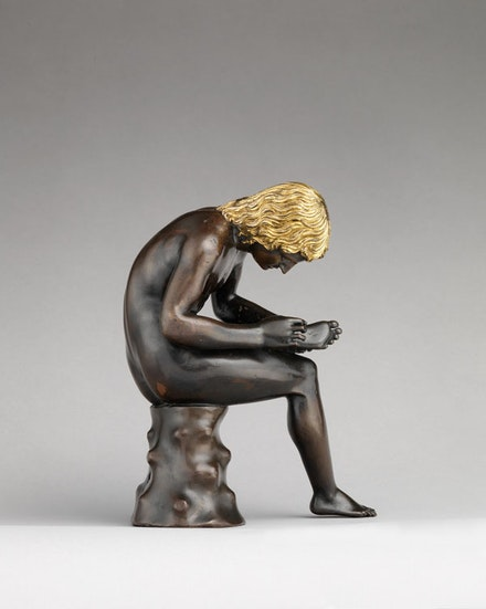 Antico (Pier Jacopo Alari Bonacolsi), <em>Spinario (Boy Pulling a Thorn from His Foot)</em>, cast ca. 1501. Bronze, partially gilt (hair) and silvered (eyes). 7 3/4 × 2 15/16 in. Courtesy the Metropolitan Museum of Art, Gift of Mrs. Charles Wrightsman, 2012.