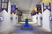 """Installation view: Michael Smith, <em>Excuse me!?!...I'm looking for the """"Fountain of Youth,""""</em>, Greene Naftali Gallery, 2015. 12 screen printed cotton pennants, 6 channel video (looped), hand-blown glass bottle, wood, CO2 tank, speakers, haute lisse, hand woven tapestry, 100% wool. Courtesy of the artist and Greene Naftali, New York."""