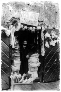 "Man with papers and paper decorations in doorway under sign ""Papirwaren, C. Schambedal"" (papershop) in Jewish ghetto, Vilna, Russia. (1922). Courtesy of The Library of Congress."