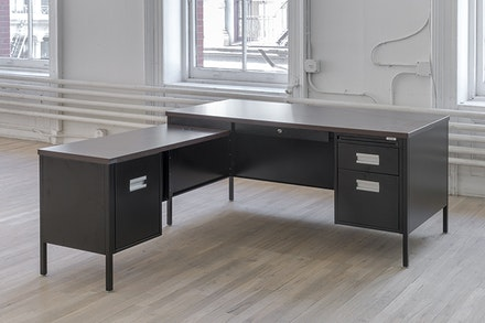 "Cameron Rowland, <i>Attica Series Desk</i>, 2016. Steel, powder coating, laminated particleboard, distributed by Corcraft, 60 x 71.5 x 28.75 inches. Rental at cost.The Attica Series Desk is manufactured by prisoners in Attica Correctional Facility. Prisoners seized control of the D-Yard in Attica from September 9th to 13th 1971. Following the inmates immediate demands for amnesty, the first in their list of practical proposals was to extend the enforcement of ""the New York State minimum wage law to prison industries."" Inmates working in New York State prisons are currently paid $0.10 to $1.14 an hour. Inmates in Attica produce furniture for government offices throughout the state. This component of government administration depends on inmate labor.Courtesy of the artist and ESSEX STREET, New York Photo: Adam Reich."