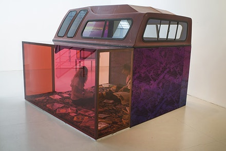 Sarah Braman, <em>Driving, sleeping, screwing, reading</em>, 2016. Truck cap, steel, aluminum, glass, rug, books, hand-dyed fabric, acrylic sticker and acrylic set paint. 81 by 100 1/2 by 101 3/4 inches. Courtesy  the artist and Mitchell-Innes & Nash.