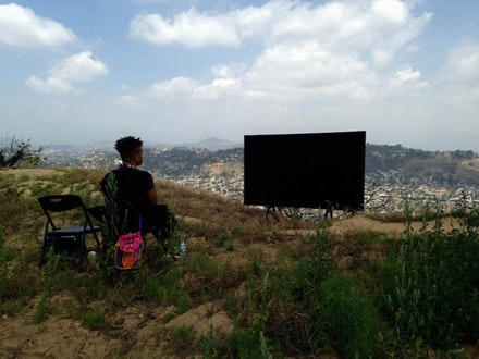 Erin Christovale facing black screen on hilltop of Elysian Park, with view of North East L.A. and the Los Angeles River. Photo: Rafa Esparza.