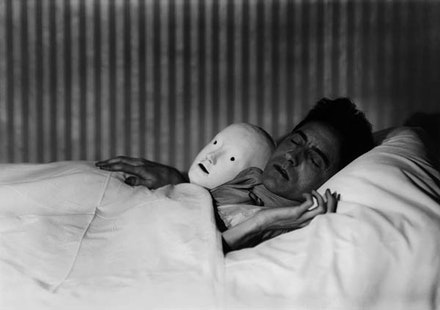 Berenice Abbott (1898 – 1991), <em>Cocteau in Bed with Mask</em>, Paris, 1927. Gelatin silver print. Printed later 10 1/2 x 13 1/2 inches. Courtesy Howard Greenberg Gallery, New York.