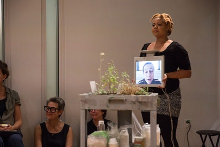 Katrina De Wees holding monitor with video of Jill Sigman in performance of Weed Heart. Photo: Scott Shaw.
