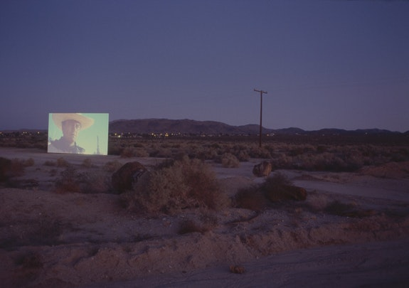 Douglas Gordon, <em>5 Year Drive-by</em>, 1995. Video Installation, dimensions variable. Installation view: Twentynine Palms, 2001. © Studio lost but found / VG Bild-Kunst, Bonn 2017. Photo: Studio lost but found / Kay Pallister. Courtesy Studio lost but found, Berlin. From <em>The Searchers</em>. 1956. USA. Directed by John Ford. Produced by Merian C. Cooper, Patrick Ford and C.V. Whitney. Distributed by Warner Bros. © Time Warner Entertainment Company. L.P.