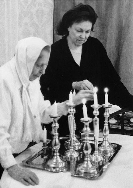 Hel&#232;ne Aylon observes her mother lighting the <em>Shabbos</em> candles, 2000. Dining Room of Borough Park, Brooklyn home. Courtesy the artist.
