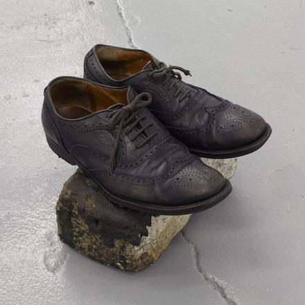 Yuji Agematsu, <em>untitled</em>, ca. 1993. Leather shoes on cobblestone. 7 1/2 × 11 × 9 1/4 inches. Photo: Thomas Müller.