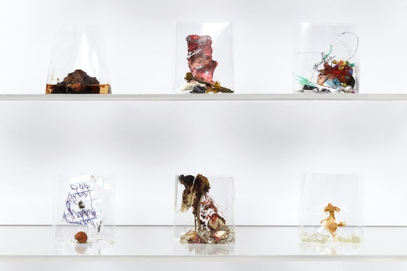 Yuji Agematsu, <em>zip; 01.01.16 . . . 12.31.16</em>, 2016 [detail]. Mixed media in cigarette cellophane wrappers (366 units) on wood backed acrylic shelves (12 units). 9 shelving units, each: 26 1/2 × 34 1/4 × 5 1/4 inches. 3 shelving units, each: 31 3/4 × 34 1/4 × 5 1/4 inches. Installation dimensions variable. Photo: Thomas Müller.
