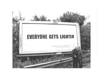 JOHN GIORNO AND UGO RONDINONE KISSING IN FRONT OF <EM>EVERYONE GETS LIGHTER BILLBOARD</EM>, 2004. PHOTO: LINA PALLOTTA.