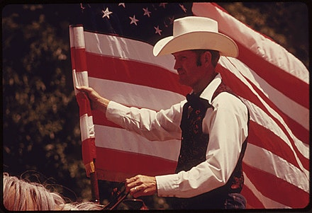 Rider with an American Flag on horseback, parade on Main Street, Cottonwood Falls, Kansas, part of the Flint Hills Rodeo, 1974. Photo by Patricia Duncan. National Archives Catalog.