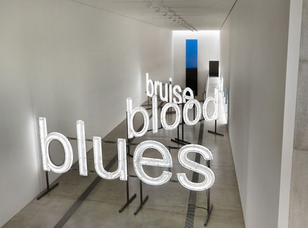 Glenn Ligon, <em>A Small Band,</em> (2015). Neon and paint. 74 3/4 x 797 1/2 inches. Courtesy of the artist; Thomas Dane Gallery, London; Luhring Augustine, New York; Regan Projects, Los Angeles © Glenn Ligon. Installation view of <em>Blue Black,</em> Pulitzer Arts Foundation, 2017. Photograph © Alise O'Brien Photography. Ellsworth Kelly's <em>Blue Black </em>(2001)<em></em>hangs in the background.