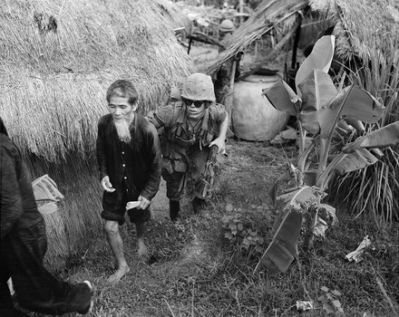 A Marine from 1st Battalion, 3rd Marines, moves a Viet Cong suspect to the rear during a search and clear operation held by the battalion 15 miles west of Da Nang Air Base. 1965.
