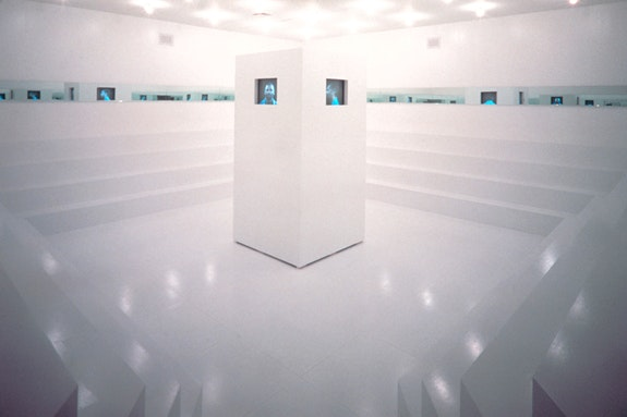 Adrian Piper, <em>What It's Like, What It Is #3</em>, 1991. Video (color, sound), constructed wood environment, four monitors, mirrors, and lighting, dimensions variable. Installation view in Dislocations, The Museum of Modern Art, New York, October 20, 1991–January 7, 1992. © Adrian Piper Research Archive Foundation Berlin.