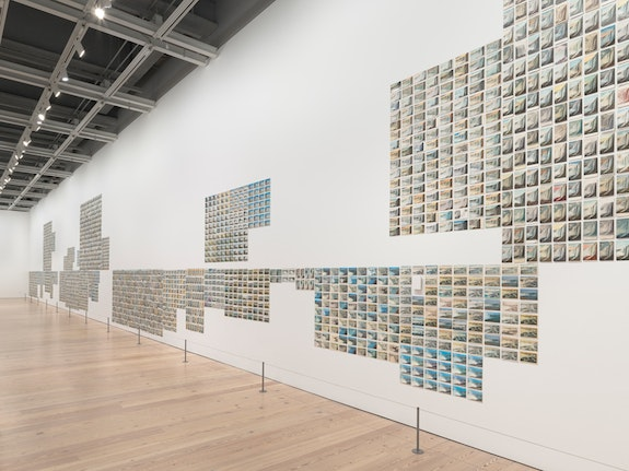 Zoe Leonard, <em>You see I am here after all</em>, 2008. Installation view, Whitney Museum of American Art. 3,883 vintage postcards, 11 x 10 1/2 x 147 ft. Courtesy Galerie Gisela Capitain, Cologne. © Zoe Leonard. Photo: Ron Amstutz.