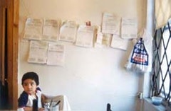 Enrique, Jr., sitting at the kitchen table with the apartment violations tacked to the wall behind him. Photo by Peiheng Tsai.