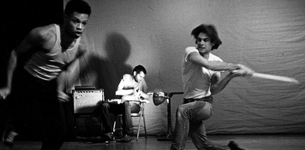 Ishmael Houston-Jones runs from John Walker, while Chris Cochrane performs on guitar. 1985. Photo: Dona Ann McAdams.