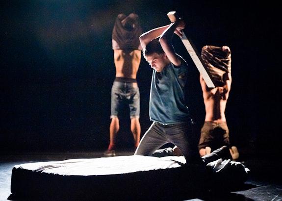 Joey Cannizzaro beats the mattress in THEM, 2010, backed by Niall Noel and Felix Cruz. Photo: Ian Douglas. Lighting: Joe Levasseur.
