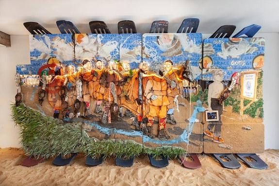 Aaron Fowler, <em>Donkey Gods</em>, 2018. Oil paint, acrylic paint, enamel paint, vinyl paint, mirror, concrete cement, hair weave, beard weave, screws, plexiglass, photo printout, pegboard, school desk chairs, Doc Martens, sneakers, socks, LED rope lights, paint brush, canvas, digital video, digital tablet, Newports, blunts, fake plants and green foam blocks on school desks, 106 x 200 x 31 inches. Courtesy Totah.