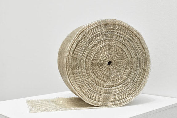 Liza Lou, <em>Roll</em>, 2008. Silver glass beads, 6.875 x 6.875 x 4.875 inches. Courtesy the artist and Lehmann Maupin, New York and Hong Kong.