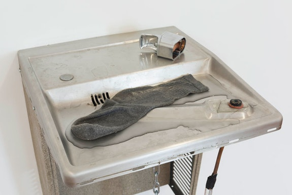 Patrick Staff, <em>Public Drunk</em>, 2018. Oasis water fountain, water, pump, vinyl tubing, aluminum bucket, PVC pipe, chain, plastic sheet, sock, snail shells, temporary tattoos, tape, approx. 44.5 x 17 x 18 inches. Courtesy the artist and Commonwealth and Council. Photo: Ruben Diaz.