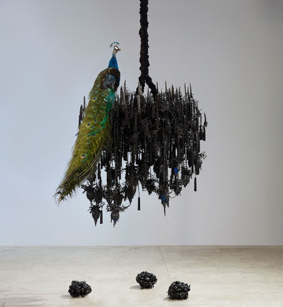 Petah Coyne,<em> Untitled #1242 (Black Snowflake)</em>, 2007-2012. Specially-formulated wax, pigment, taxidermy, candles, tassels, ribbons, hand-blown glass bulbs, chicken-wire fencing, wire, steel, cable, cable nuts, sash weight, quick-link shackles, jaw-to-jaw swivel, silk/rayon velvet, 3/8rdquo; Grade 30 proof coil chain, Velcro, thread, plastic, 71 x 75 x 50 inches. &copy; Petah Coyne. Courtesy Galerie Lelong &amp; Co., New York.