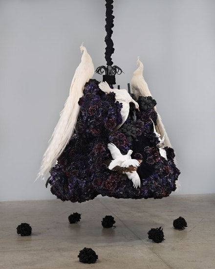 "Petah Coyne, <em>Untitled #1375 (No Reason Except Love: Portrait of a Marriage)</em>, 2011-12. Specially-formulated wax, pigment, silk flowers, taxidermy, chandelier, candles, ribbons, black sand from pig iron casting, resin, paint, black pearl-headed hat pins, chicken-wire fencing, wire, cable, cable nuts, quick-link shackles, jaw-to-jaw swivel, silk/rayon velvet, 3/8"" Grade 30 proof coil chain, Velcro, thread, plastic, 81 x 71 x 66.5 inches. © Petah Coyne. Courtesy Galerie Lelong & Co., New York."