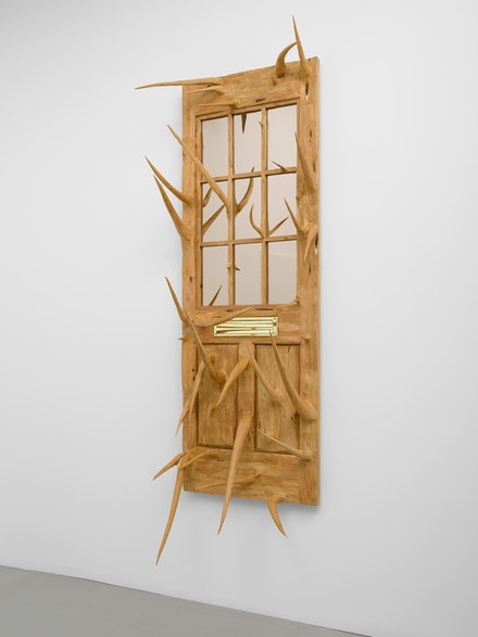 Hugh Hayden, <em>Cable News</em>, 2018. Sculpted post cedar (Juniperus ashei) with mirror and hardware, 101 x 31 1/2 x 19 1/2 inches. © Hugh Hayden. Courtesy Lisson Gallery.