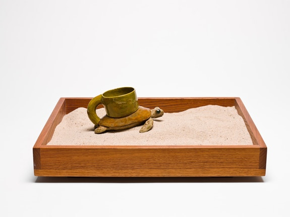 Ken Price, <em>Blind Sea Turtle Cup</em>, 1968. Ceramic sculpture in teakwood tray with sand in glass vitrine on wood pedestal. Tray: 2 x 15 x 12 inches. Ceramic: 2 7/8 x 3 7/8 x 5 5/8 inches. © Estate of Ken Price, Courtesy Matthew Marks Gallery.