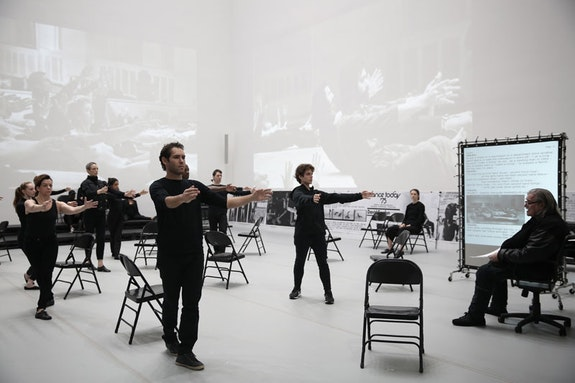 David Gordon. <em>THE MATTER @ MOMA/2018</em>. 2018. Performance. Performed in <em>Judson Dance Theater: The Work Is Never Done, The Museum of Modern Art,</em> New York, September 16, 2018–February 3, 2019. Performers: Carmella Lauer, Pam Tanowitz, Lauren Fergusson, Ambika Raina, Darrin Wright, Paul Hamilton, Colin Gee, Erez Milatin, Lydia Chrisman (seated), David Gordon. Digital image © 2018 The Museum of Modern Art, New York. Photo: Paula Court.