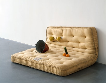 Sarah Lucas, <em>Au Naturel</em>, 1994. Mattress, melons, oranges, cucumber, and water bucket, 33 1/8 x 66 1/8 x 57 inches. © Sarah Lucas. Courtesy Sadie Coles HQ, London.