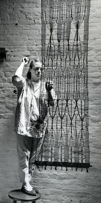 <p>Lenore Tawney with<em>Vespers</em>, South Street studio, 1961. Photo: Ferdinand Boesch, courtesy Lenore G. Tawney Foundation.</p>