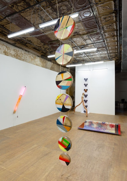 Jeffrey Gibson, <em>Drum Column</em>, 2012. Acrylic paint, elk hide, drums made by Jesse McMann-Sparvier, rawhide lacing and artificial sinew, 120 x 28 x 5 inches. Installation view: <em>One becomes the other</em>, PARTICIPANT Inc., New York, 2012. Photo: Etienne Frossard. © Jeffrey Gibson, courtesy Sikkema Jenkins & Co., New York; Kavi Gupta, Chicago; and Roberts Projects, Los Angeles.